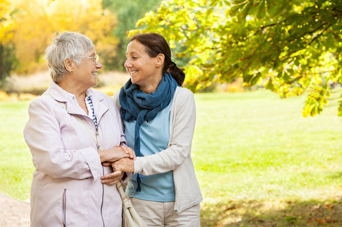 Happy senior woman and carer go walking in the park